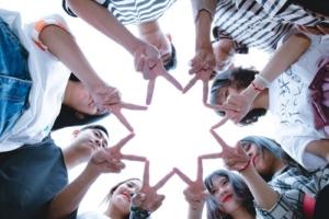 Opiskelijaryhmä muodostaa sormilla tähden