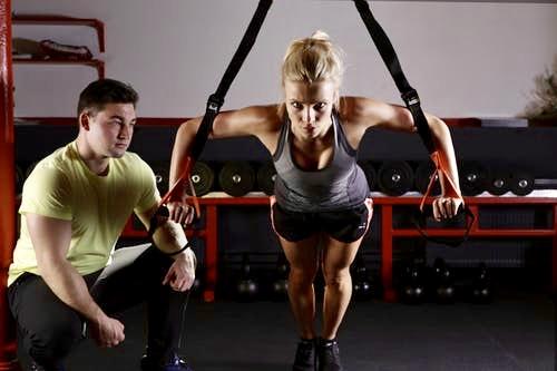 Nainen treenaa valmentajan valvovan silmän alla