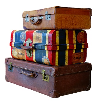 Kolme vanhaa matkalaukkua pinossa