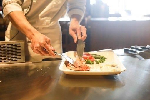 Kokki asettelee ruoka-annosta lautaselle