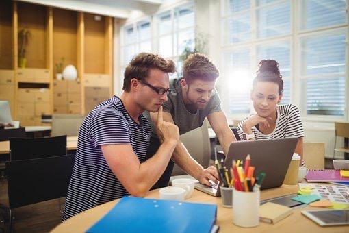 Kolme lähiesimiestyön ammattitutkinnon opiskelijaa saman tietokoneen äärellä